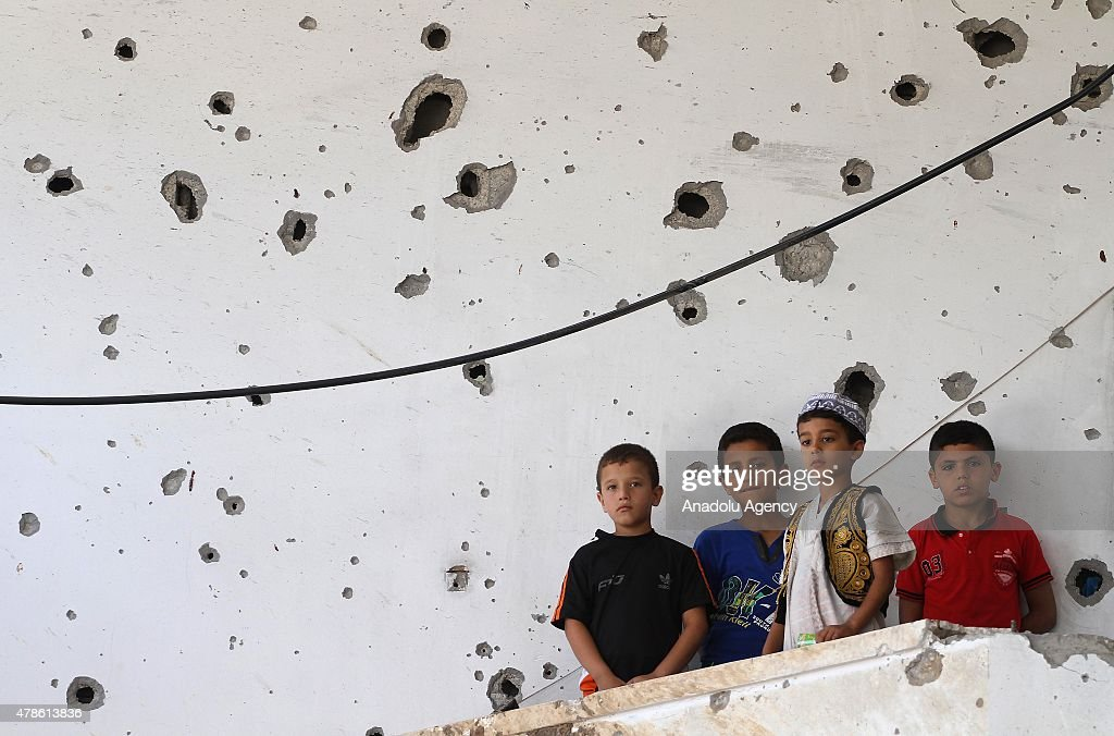 Palestinian kids stand in al-Murabitin mosque that was damaged in Israeli attacks, during the second Friday prayer of the Islam's holy fasting month of Ramada in Shejaiya neighborhood of Gaza on June 26, 2016.