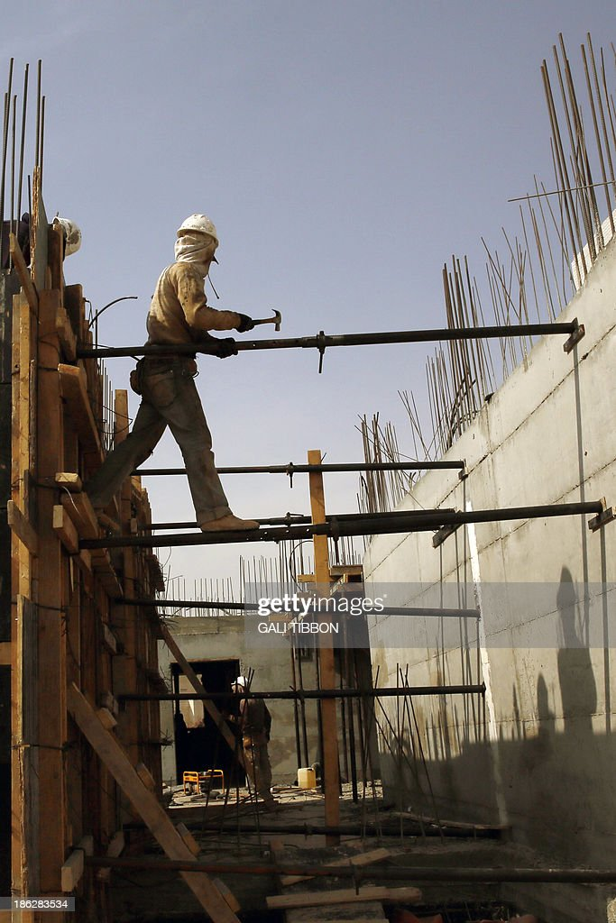 Palestinian laborers work on a construction site in Ramat Shlomo, a Jewish settlement in the mainly Palestinian eastern sector of Jerusalem, on October 30, 2013. Israel freed 26 veteran Palestinian prisoners overnight in line with commitments to the US-backed peace process, but moved in tandem to ramp up settlement in annexed east Jerusalem.