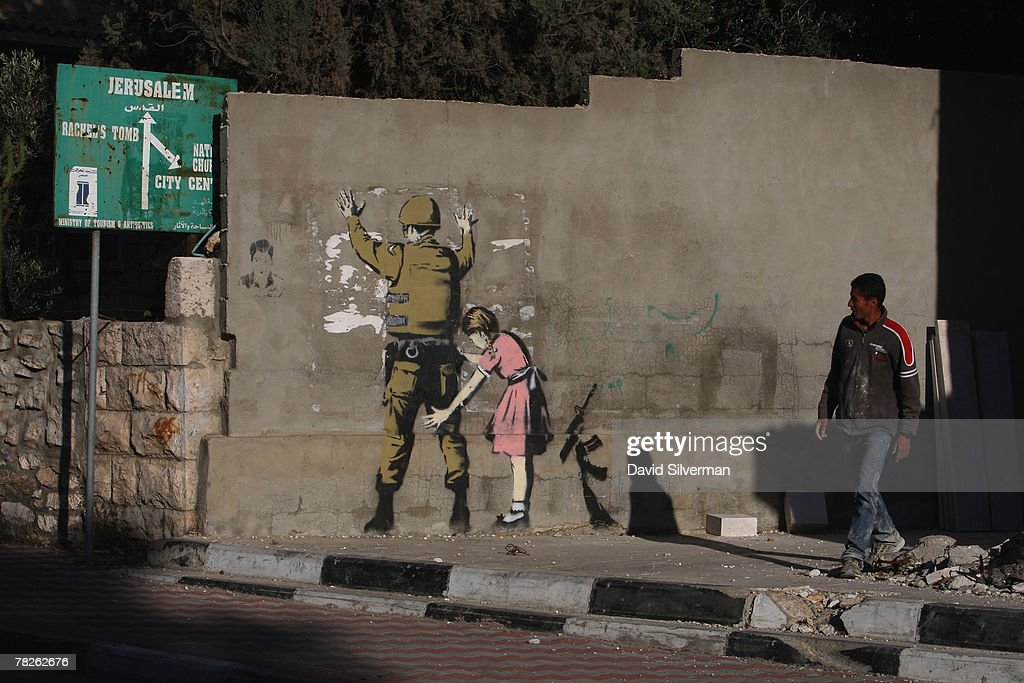 A Palestinian labourer looks up at a wall painting by elusive British graffiti artist Banksy December 5, 2007 on a wall in the biblical city of Bethlehem in the West Bank. The Bristol-born artist has adorned Israel's West Bank separation barrier and Bethlehem walls with new images, including this one of a soldier being frisked by a young girl and a dove wearing a flak jacket. His works, along with those of other international artists, are part of an exhibition called Santa's Ghetto.