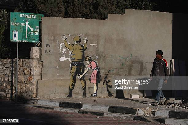 Palestinian labourer looks up at a wall painting by elusive British graffiti artist Banksy December 5 2007 on a wall in the biblical city of...