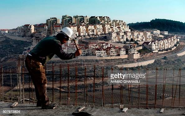 Palestinian labourer works on a construction site in the Israeli settlement of Efrat situated on the southern outskirts of the West Bank city of...