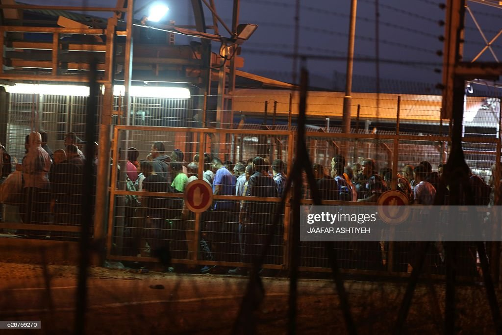 Palestinian labourers pass between fences and gates at the Israeli army crossing of Eyal as they cross from the West Bank town of Qalqilya to work in Israel early on May 1, 2016. Thousands of Palestinians enter Israel to work every day after receiving permits. / AFP / JAAFAR