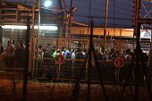 Palestinian labourers pass between fences and gates at the Israeli army crossing of Eyal as they cross from the West Bank town of Qalqilya to work in...