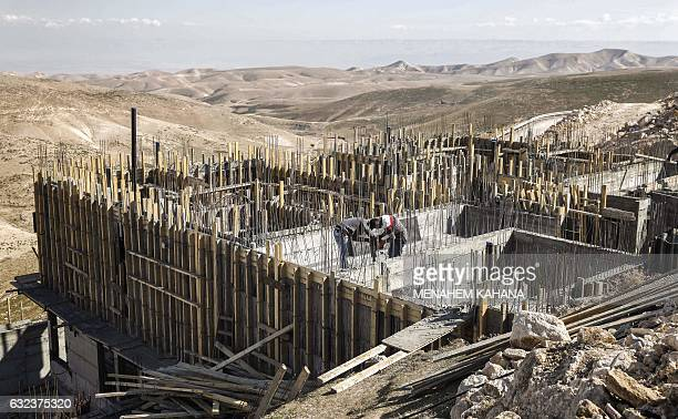 Palestinian labourers work at a construction site in a new housing project in the Israeli settlement of Maale Adumim east of Jerusalem on January 22...