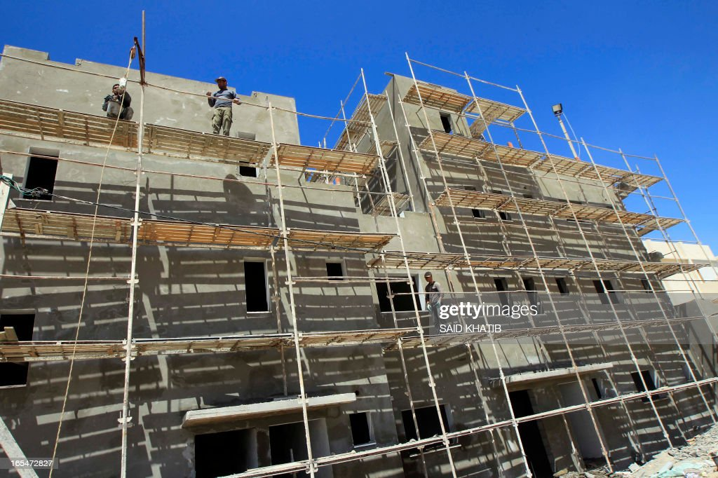 Palestinian labourers work at a construction site on April 4, 2013, as part of a re-housing Saudi-funded project led by the United Nations Relief and Works Agency for Palestine Refugees (UNRWA) in Rafah, in the southern Gaza Strip. The United Nations announced the previous day it is to provide financial support to thousands of Gaza families affected by last year's conflict with Israel thanks to a Saudi donation of nearly $16 million. AFP PHOTO / SAID KHATIB