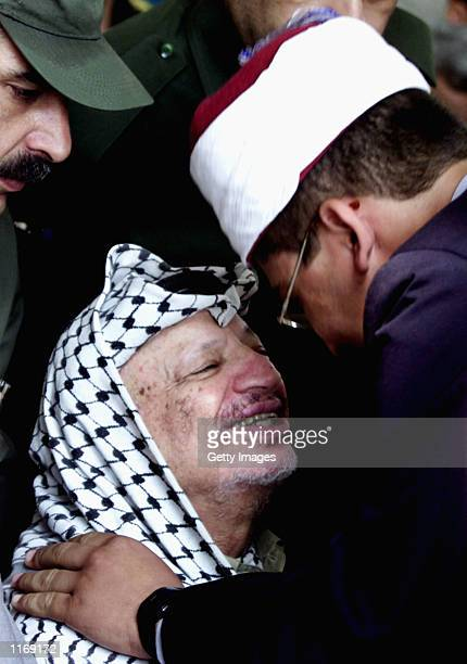 Palestinian leader Yasser Arafat kisses a Palestinian student during the Muslim celebration of Miraj alNabi at a mosque October 13 2001 in Gaza City...