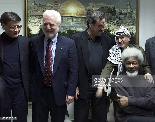 Palestinian leader Yasser Arafat poses with Palestinian poet Mahmoud Darwish US writer Russell Banks US director Oliver Stone and Nobel literature...