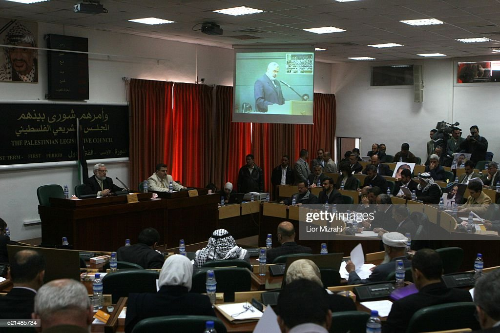 Palestinian legislators listen to incoming Palestinian Prime Minister Ismail Haniyeh, seen on a screen from Gaza, during a special session at the Palestinian Legislative Council in the West Bank town of Ramallah on Monday March 27, 2006. Haniyeh told parliament that the new government, expected to win a vote of confidence on Tuesday or Wednesday, would be ready for a dialogue with the 'Quartet' of mediating powers.