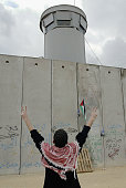Palestinian makes the victory salute to Israeli soldiers manning a guard tower above Israel's security wall November 9 2003 during a protest on the...