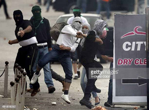 Palestinian male and female demonstraters throw stones towards Israeli security forces during clashes in Beit El near the West Bank city of Ramallah...