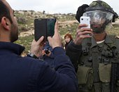 A Palestinian man and a member of the Israeli security forces take pictures of each other with their mobile phones after Palestinians from the West...