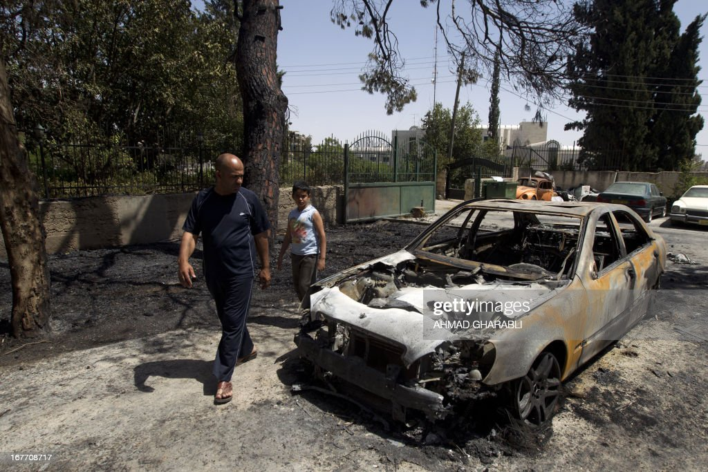 A Palestinian man and his son look at a burnt vehicle that was, according to them, fired by Israelis on April 28, 2013 in Jerusalem at the start of the day-long holiday of Lag Baomer that commemorates the Jewish scholar's death. Traditionally, Thousands of religious Jews light large bonfires all night long and visit the shrine of Bar Yochai, one of the most prominent sages in Jewish history, during the holiday.