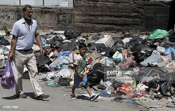 A Palestinian man and his son walk past piles of accumulated rubbish in the Palestinian refugee camp of Shuafat in east Jerusalem on June 12 2015 The...