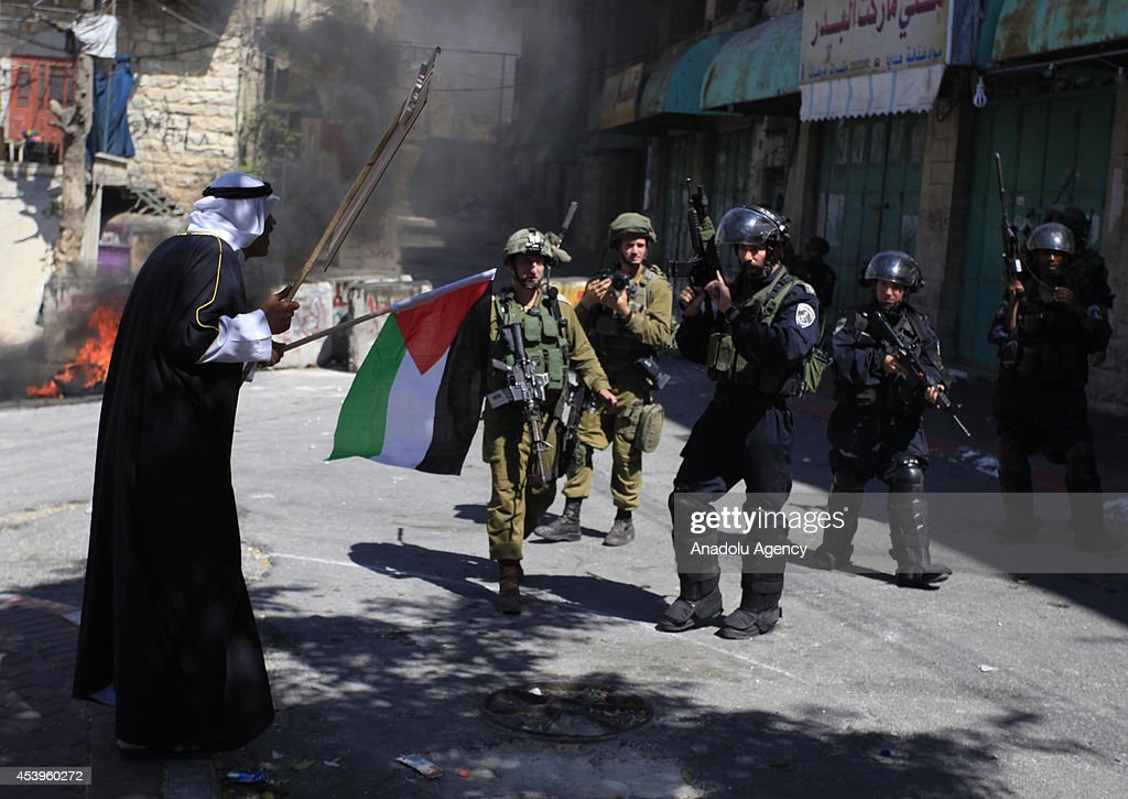 A Palestinian man argues with the members of the Israeli security forces after Palestinian protestors following a protest to show support for resistance movement Hamas in Hebron, West Bank on August 22, 2014.