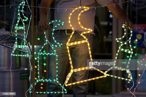 A Palestinian man arranges neon lights and other decorations for the upcoming Muslim holy month of Ramadan at his store in Jerusalem on August 8 2010...