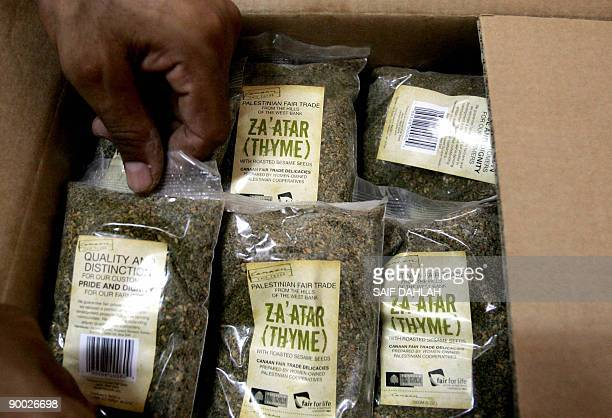 A Palestinian man arranges sachets of thyme into a box at a cooperative of the Palestinian fairtrade association in the West Bank village of Burkin...