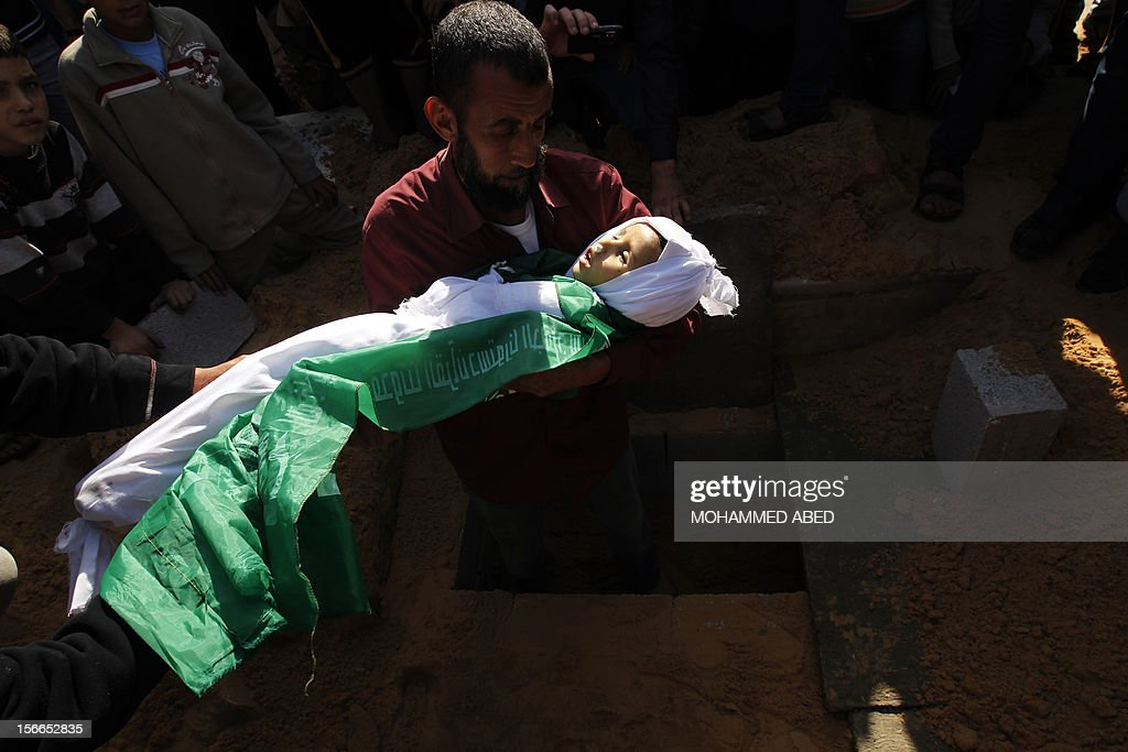 A Palestinian man barries the body of Tamer Abu Sefan, three and a half years old, during a funeral in the village of Beit Lahia, in the northern Gaza Strip on November 18, 2012. A ground invasion of the Gaza Strip would lose Israel much international sympathy and support, British Foreign Secretary William Hague warned. AFP PHOTO/MOHAMMED ABED