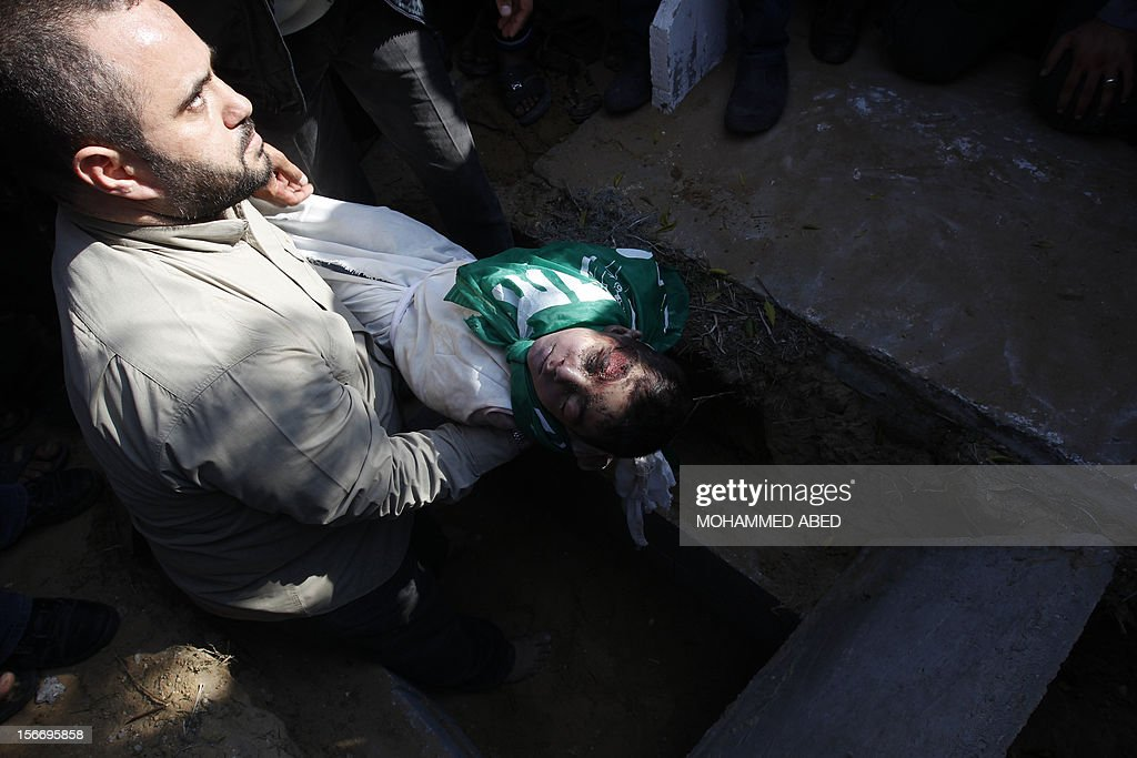 A Palestinian man buries the body of a child from the al-Dallu family during the funeral of several members from the same family in Gaza City on November 19, 2012. An Israeli missile struck a three-story building in Gaza City on November 18, killing many members of the al-Dallu family - five of them children - and two of their neighbours, medics said.