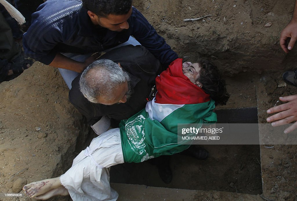 A Palestinian man buries the body of a child from the al-Dallu family, draped in Palestinian and Hamas flags, during the funeral of several members from the same family in Gaza City on November 19, 2012. An Israeli missile struck a three-story building in Gaza City on November 18, killing many members of the al-Dallu family - five of them children - and two of their neighbours, medics said.
