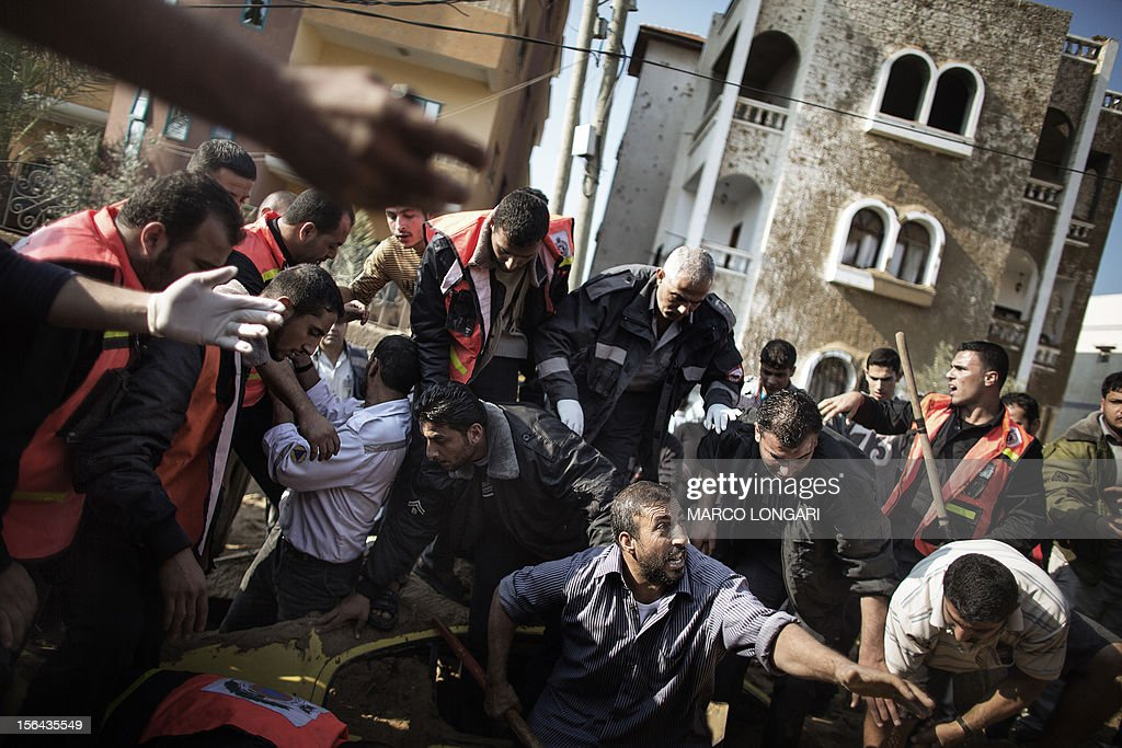 A Palestinian man calls for help as he and others try to save a man trapped under his car just after an Israeli air raid on the area of Twaam in the northern Gaza town of Beit Lahia on November 15, 2012. Israeli air strikes have killed more than ten Gazans, including top Hamas commander Ahmed Jaabari, as three Israelis die when a rocket strikes a house, in the latest flareup of tit-for-tat fighting.