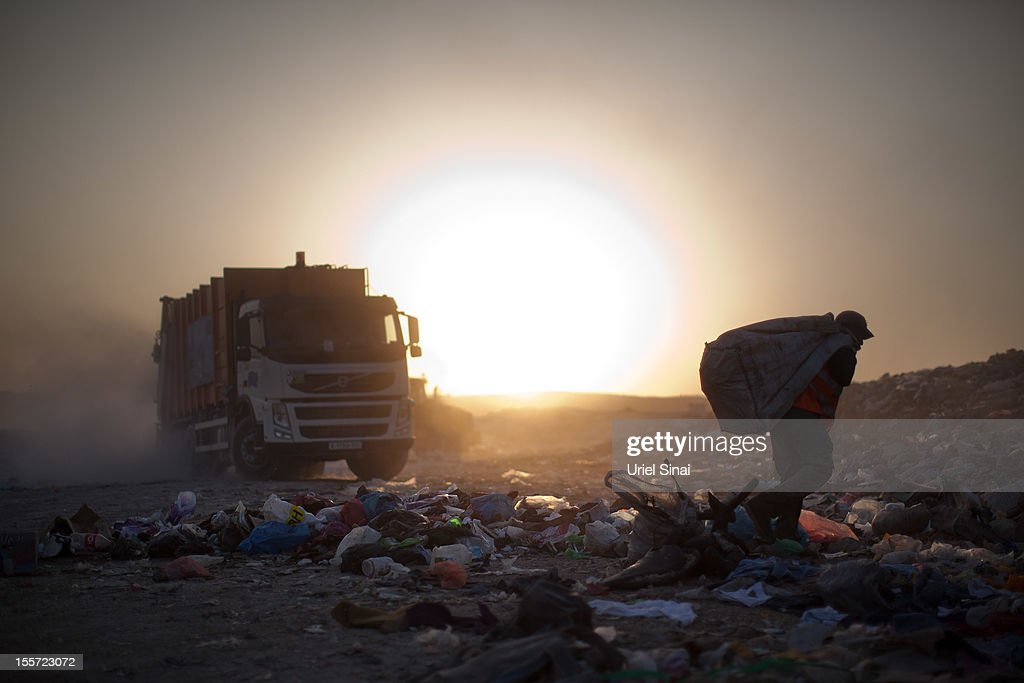 A Palestinian man carries a bag as he sifts through a garbage dump on November 7, 2012 south of Hebron, West Bank. About 40 Palestinain men and children work at the West Bank garbage dump looking for clothing, metal and wood discarded, in large part, from the Jewish settelment in the region.
