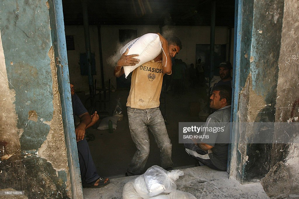 A Palestinian man carries a bag of wheat flour distributed at an aid distribution centre of the United Nations Relief and Works Agency (UNRWA) in Rafah in the southern Gaza Strip on September 10, 2013.