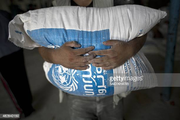 A Palestinian man carries a bag of wheat flour distributed at an aid distribution centre of the United Nations Relief and Works Agency in Rafah in...