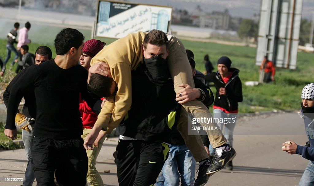 A Palestinian man carries a fellow injured protestor during clashes with Israeli security forces at the entrance of the Jalama checkpoint, near the West Bank city of Jenin, on February 15, 2013. AFP PHOTO/SAIF DAHLAH