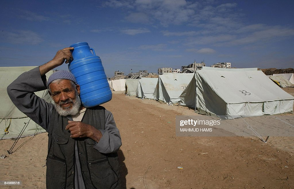 A Palestinian man carries a plastic can as he walks past tents erected to house those who lost their homes during the 22day Israeli offensive in...
