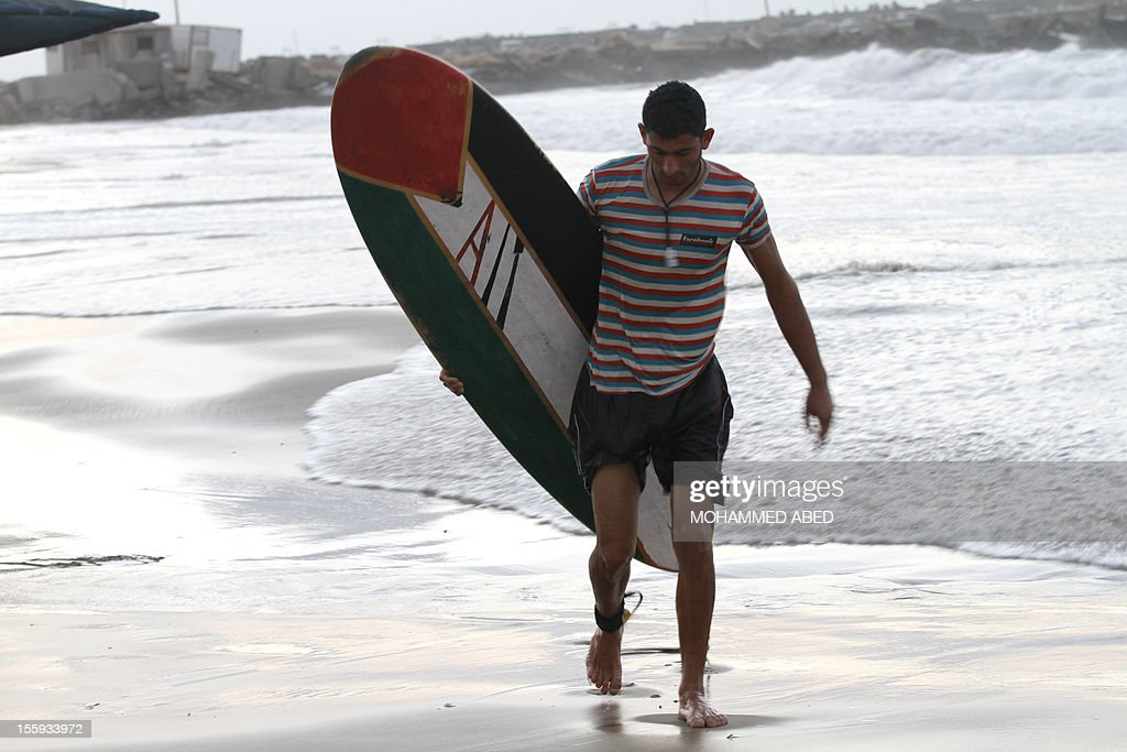 A Palestinian man carries a surf board bearing the colours of the national flag, off the coast of the Gaza Strip in the Mediterranean Sea on November 9, 2012. Life in the poor and crowded Gaza Strip is going to get harsher still unless action is taken now, according to a new United Nations report.