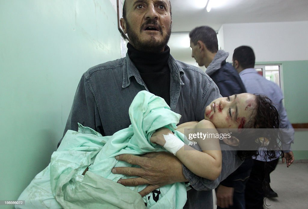 A Palestinian man carries a wounded child at a hospital following an Israeli air raid in Beit Lahia, northern Gaza Strip, on November 17, 2012. Israeli air strikes hit the cabinet headquarters of Gaza's Hamas government, after militants fired rockets at Jerusalem and Tel Aviv as Israel called up thousands more reservists in readiness for a potential ground war. AFP PHOTO/MOIZ SALHI