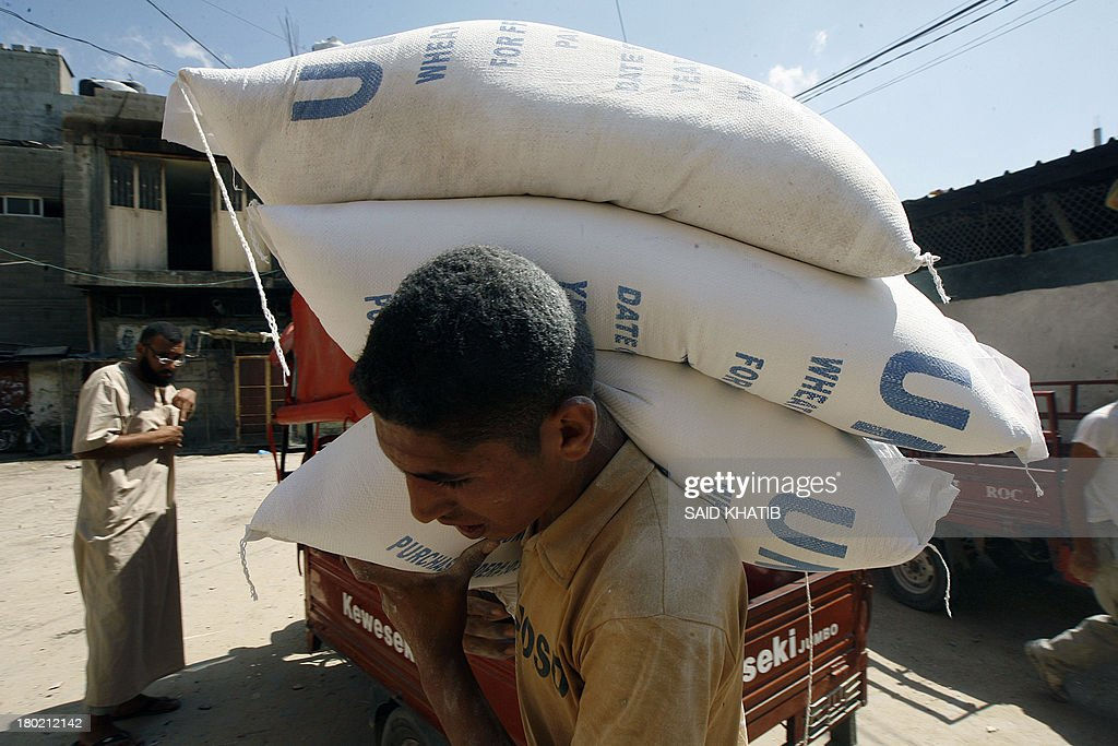 A Palestinian man carries bags of wheat flour distributed at an aid distribution centre of the United Nations Relief and Works Agency (UNRWA) in Rafah in the southern Gaza Strip on September 10, 2013.