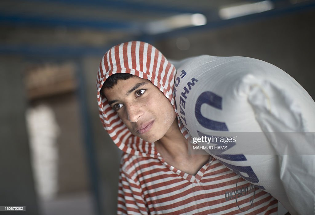 A Palestinian man carries bags of wheat flour distributed at an aid distribution centre of the United Nations Relief and Works Agency (UNRWA) in Gaza City on September 17, 2013. UNRWA operates through 11,000 staff in over 200 installations across the Gaza Strip, providing education, health care and social services to Palestinian refugees.