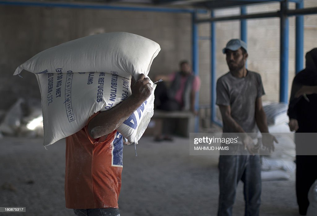 A Palestinian man carries bags of wheat flour distributed at an aid distribution centre of the United Nations Relief and Works Agency (UNRWA) in Gaza City on September 17, 2013. UNRWA operates through 11,000 staff in over 200 installations across the Gaza Strip, providing education, health care and social services to Palestinian refugees. AFP PHOTO / MAHMUD HAMS