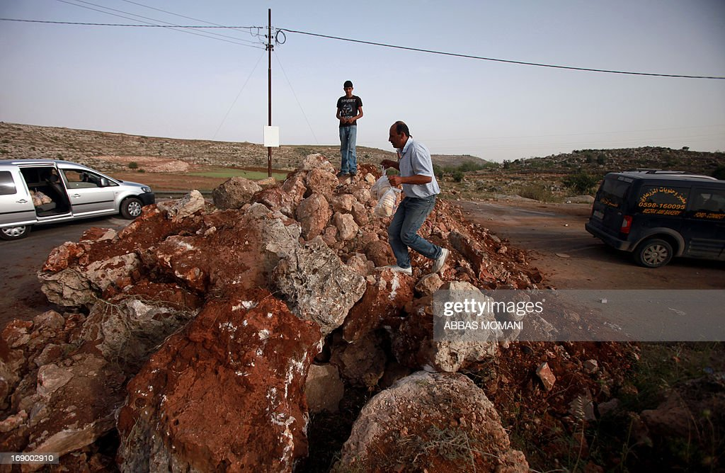 A Palestinian man carries bread over a makeshift roadblock to the other side of the road leading to the village of Deir Jarir east of Ramallah on May 18, 2013. Israeli soldiers closed the road leading to Deir Jarir due to ongoing clashes with Palestinian demonstrators. AFP PHOTO/ABBAS MOMANI