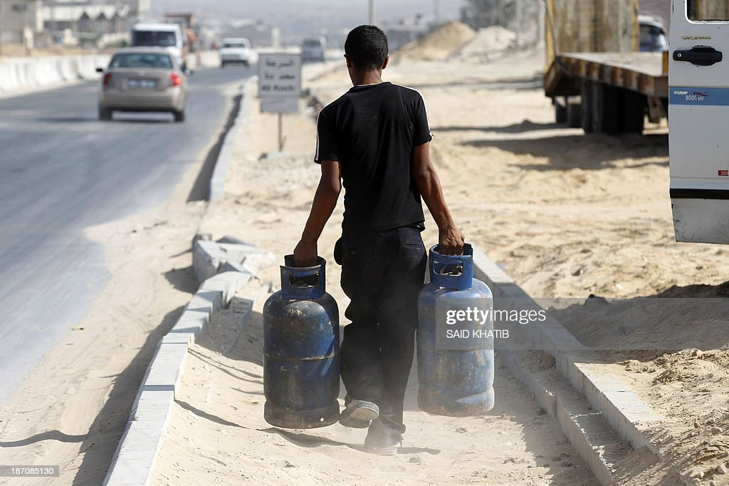 A Palestinian man carries cooking gas bottles after they were refilled in Rafah, in the southern Gaza Strip on November 6, 2013. Palestinian officials said Israel has limited the quantity of cooking gas entering into Gaza, which causes a shortage.