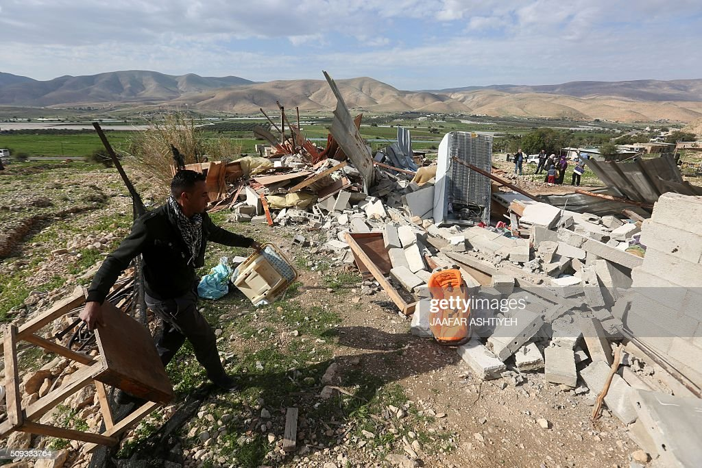 A Palestinian man carries furniture after his house was demolished by Israeli authorities on February 10, 2016 in the West Bank village of Jeftlek, in the Jordan valley near Jericho. Israel often demolishes buildings constructed without the required Israeli permits in Area C of the West Bank, which is under full Israeli control. / AFP / JAAFAR ASHTIYEH