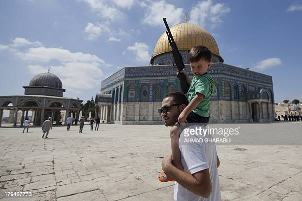 A Palestinian man carries on his shoulders a child holding a fake gun outside the Dome of Rock at the AlAqsa Mosque compound Islam's third most holy...