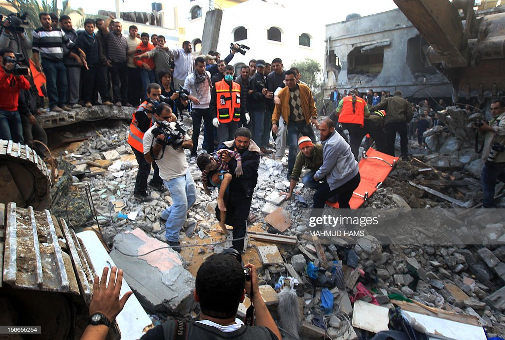 A Palestinian man carries the body of a child from the al-Dallu family out from the rubble after an Israeli missile struck a family home killing at least seven members of the same family in Gaza City on November 18, 2012.