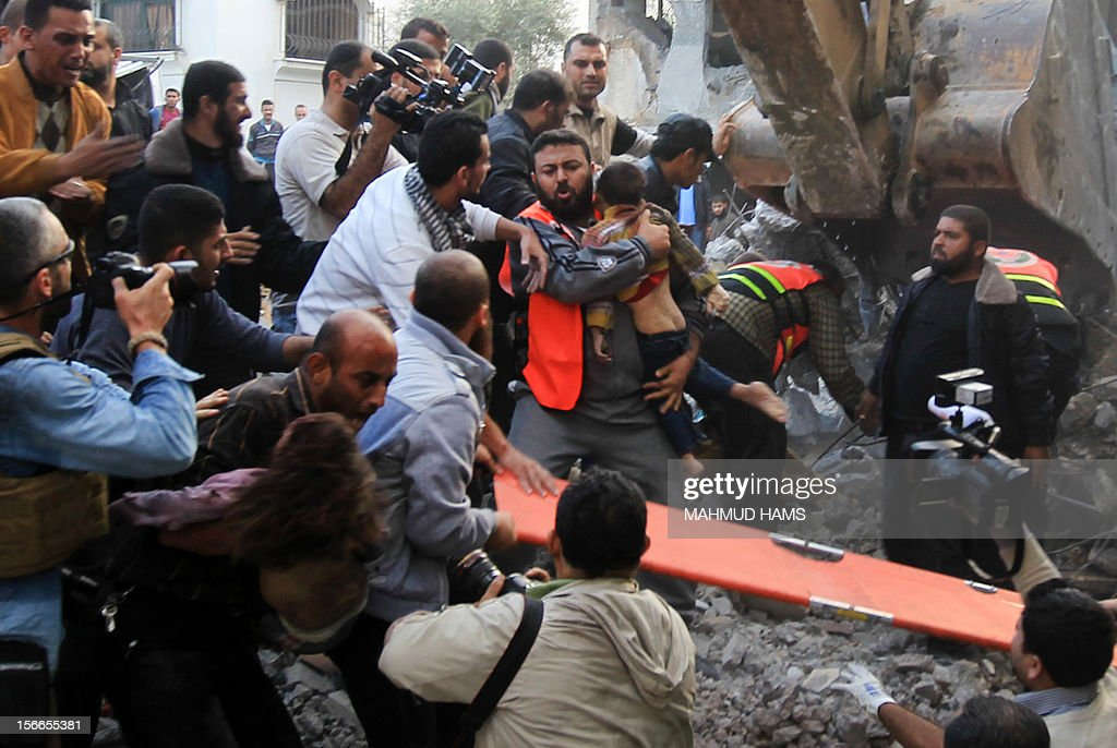 A Palestinian man carries the dead body of a child from the al-Dallu family out from the rubble after an Israeli missile struck a family home killing at least seven members of the same family in Gaza City on November 18, 2012. AFP PHOTO/MAHMUD HAMS