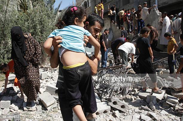 A Palestinian man carrying a child makes his way through debris as people inspect the remains of a house belonging to a member of the Islamist Hamas...