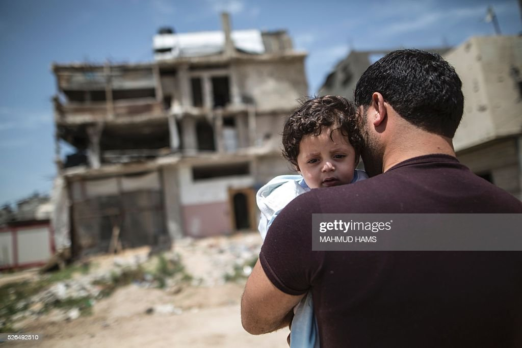 A Palestinian man carrying a child walks past buildings destroyed during the 50-day war between Israel and Hamas-led militants in the summer of 2014, on April 30, 2016, in Gaza City. Reconstruction aid to over 1,000 families in Gaza has been suspended due to a lack of materials, the United Nations said on April 28, after Israel banned the private import of cement over corruption claims. / AFP / MAHMUD