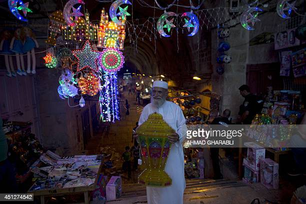 A Palestinian man carrying a lantern walks past decorated shops at the entrance of the AlAqsa mosque compound in the old city of Jerusalem on June 26...