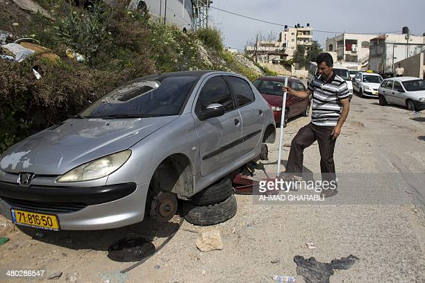 A Palestinian man changes the tyres of his car on March 24 2014 after suspected Jewish vandals punctured the tyres of dozens of Palestinian cars in...