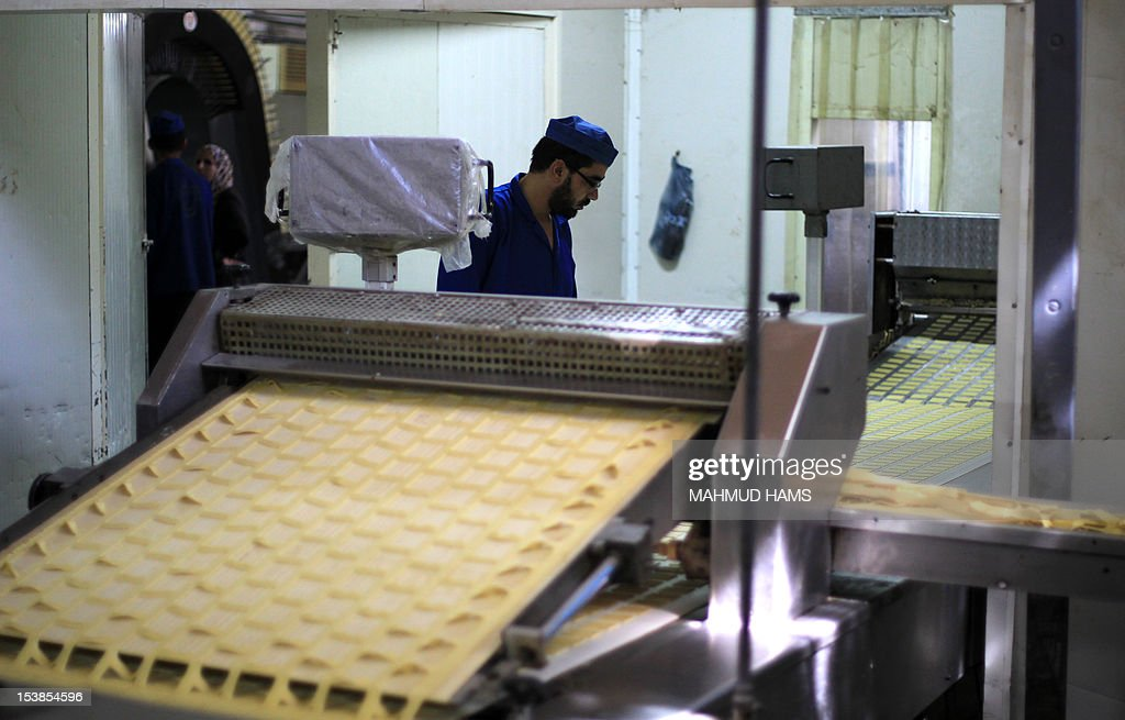 A Palestinian man checks biscuits at the al-Awda factory in Deir al-Balah, in the central Gaza strip, on October 10, 2012. The World Food Program (WFP) will export the biscuits to United Nation run schools in the Israeli occupied Palestinian West Bank, the first time since 2006 when the Gaza Strip was put under an Israeli blockade.