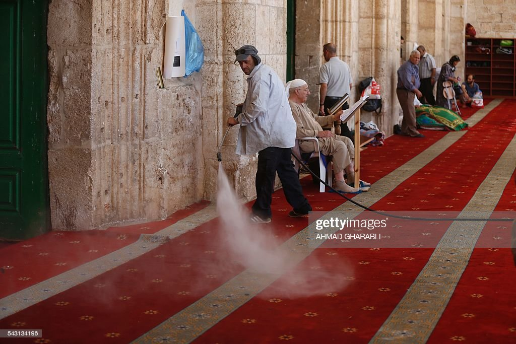 A Palestinian man clears the damage at the entrance of Al-Aqsa Mosque in Jerusalem's Old City after clashes erupted at the compound between Palestinians and Israeli police on June 26, 2016 during the holy month of Ramadan. Israeli police at Jerusalem's Al-Aqsa mosque compound clashed with Muslims protesting Jewish visits there as the Islamic holy month of Ramadan approached its climax, Palestinians said. / AFP / AHMAD