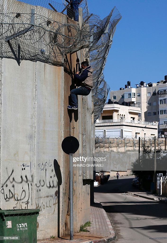 A Palestinian man climbs using a rope over a section of Israel's controversial separation barrier that separates the West Bank from Jerusalem on February 12, 2016, in Beit Hanina in east Jerusalem. Many Palestinians from the West Bank cross illegally into Israel everyday in search for work. / AFP / AHMAD GHARABLI