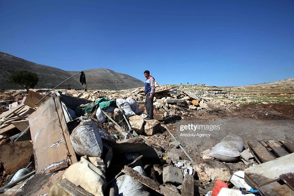 A Palestinian man collects his belongings from the debris of his tin-plated house, which was demolished by Israeli authorities at Tana Village in Nablus, West Bank on February 9, 2016.
