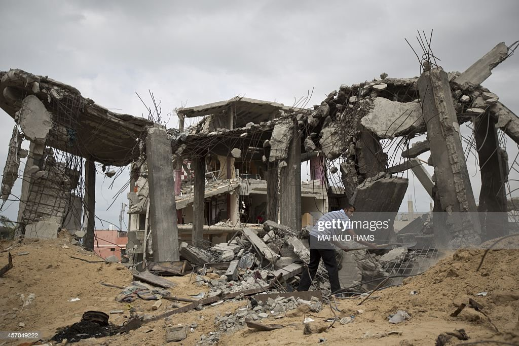 A Palestinian man collects rubble near destroyed buildings in alTufah east of Gaza City on October 11 ahead of a donors conference in Cairo aimed at...