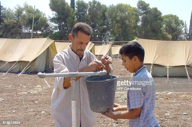 A Palestinian man collects water along with his son from a tap setup close to United Nations donated tents 11 August 2002 in the West Bank...
